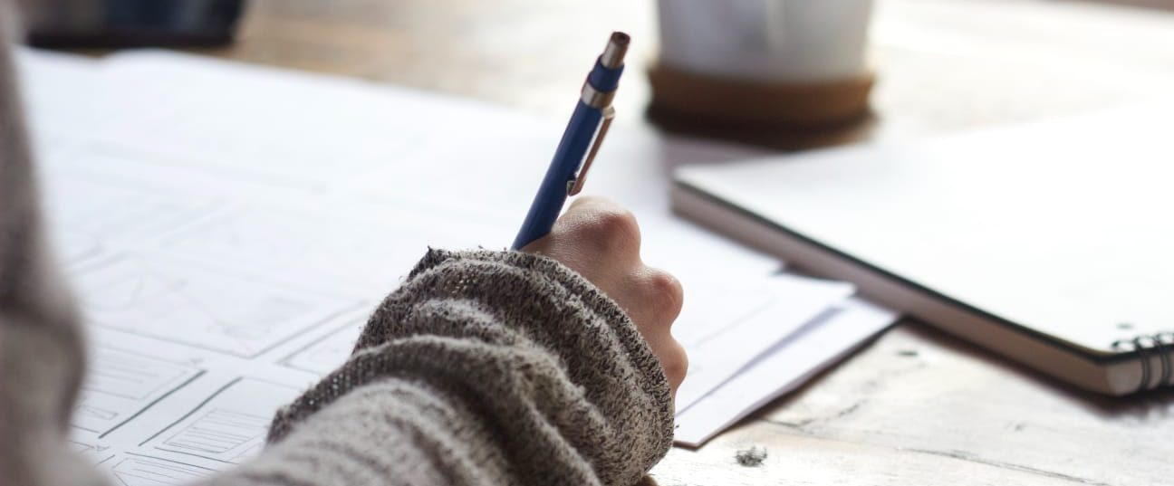 Person writing on a desk with papers, a notebook and a mug